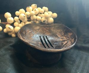 Hand carved coconut shell soap dish with drainage holes.